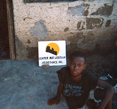 A picture of a child with a sign that says Center for Liberian Assistance